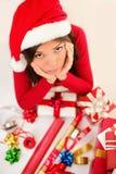 Mujer triste de santa de la Navidad que envuelve los regalos Foto de archivo