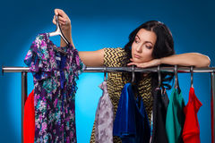 Mujer triste debajo del estante de la ropa con los vestidos Imagen de archivo