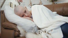 Mujer triste, deprimida del enfermo de cáncer que miente en el sofá y dolores metrajes