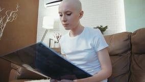 Mujer triste, deprimida del enfermo de cáncer que mira su radiografía almacen de metraje de vídeo