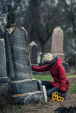 Mujer triste en de tacto de luto amado su lápida mortuaria Imagenes de archivo