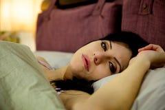 Mujer triste en el pensamiento de la cama Foto de archivo