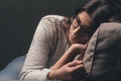 Mujer triste en el sofá en casa Imagenes de archivo