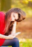 Mujer triste en parque con el teléfono Imagenes de archivo