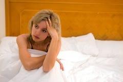 Mujer triste en una cama Imágenes de archivo libres de regalías