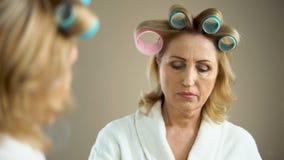 Mujer triste envejecida con los bigudíes de pelo y maquillaje que mira la reflexión de espejo metrajes
