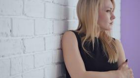 Mujer triste hermosa de Yound que presenta cerca de la pared de ladrillo blanca metrajes