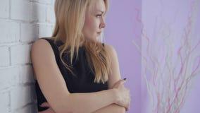 Mujer triste hermosa de Yound que presenta cerca de la pared de ladrillo blanca almacen de video