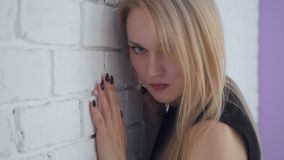 Mujer triste hermosa de Yound que presenta cerca de la pared de ladrillo blanca almacen de metraje de vídeo