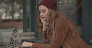 Mujer triste hermosa que se sienta solamente en restaurante del aire libre almacen de video