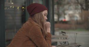 Mujer triste hermosa que se sienta solamente en restaurante del aire libre almacen de metraje de vídeo