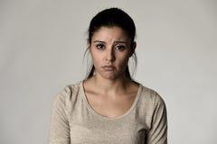 Mujer triste hispánica hermosa joven seria y en cuestión en la expresión facial deprimida preocupante Imagen de archivo