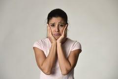 Mujer triste hispánica hermosa joven seria y en cuestión en la expresión facial deprimida preocupante foto de archivo libre de regalías