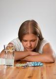 Mujer triste joven con las píldoras Fotos de archivo