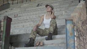 Mujer triste joven en el uniforme militar que se sienta en las escaleras concretas frías en el edificio abandonado Zapatos de tac metrajes
