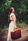 Mujer triste joven hermosa con la maleta a disposición que se coloca en el camino Imagen de archivo