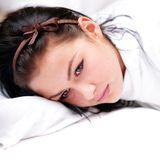 Mujer triste pensativa que miente en una almohadilla Foto de archivo