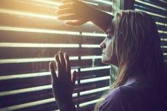 Mujer triste por la ventana Imagen de archivo