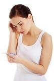 Mujer triste, preocupante con la prueba de embarazo. Fotografía de archivo