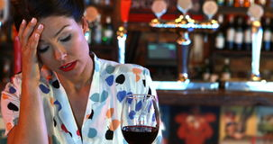 Mujer triste que come vino rojo almacen de video