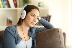 Mujer triste que escucha la música en casa Foto de archivo