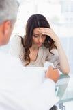 Mujer triste que escucha su docter que habla de una enfermedad Imágenes de archivo libres de regalías