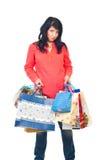 Mujer triste que lleva bolsos pesados Imagen de archivo libre de regalías