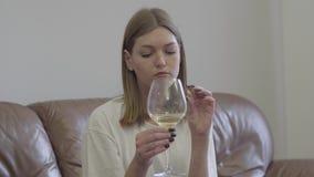 Mujer triste que lleva a cabo el anillo de bodas debajo de la copa de vino Problemas de la familia Traición, divorcio, concepto d almacen de video