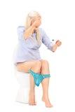 Mujer triste que lleva a cabo la prueba de embarazo asentada en retrete Imagen de archivo