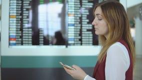 Mujer triste que mecanografía en smartphone en aeropuerto almacen de metraje de vídeo