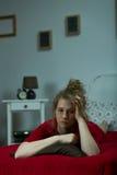 Mujer triste que miente en cama Fotos de archivo