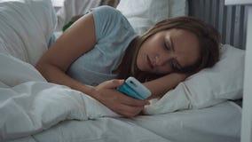 Mujer triste que miente en cama usando smartphone y que intenta caer dormido almacen de metraje de vídeo
