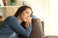 Mujer triste que mira el canal una ventana que se sienta en un sofá Fotos de archivo libres de regalías