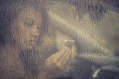 Mujer triste que mira en el teléfono móvil y que lee el mensaje en la ventana con gota de lluvia en el coche Imágenes de archivo libres de regalías