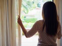 Mujer triste que mira hacia fuera una ventana, dentro Imagenes de archivo
