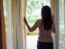 Mujer triste que mira hacia fuera una ventana, dentro Foto de archivo