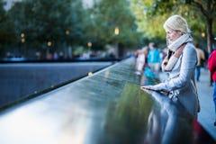 Mujer triste que mira los nombres del monumento del World Trade Center foto de archivo