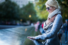 Mujer triste que mira los nombres del monumento del World Trade Center imagen de archivo libre de regalías