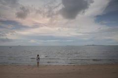 Mujer triste que se coloca en la playa que mira el mar Fotografía de archivo