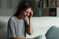 Mujer triste que se queja en casa en la noche fotografía de archivo