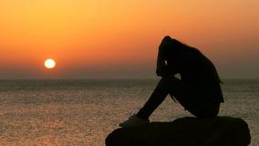 Mujer triste que se queja en la puesta del sol en la playa almacen de metraje de vídeo