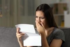 Mujer triste que se queja leyendo una letra en la noche Fotografía de archivo