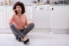 Mujer triste que se sienta al lado del lavaplatos da?ado Calling Technician imagen de archivo