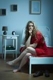 Mujer triste que se sienta en cama Imagen de archivo libre de regalías