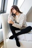 mujer triste que se sienta en cama en casa Imagen de archivo libre de regalías