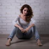 Mujer triste que se sienta en el piso Imagenes de archivo