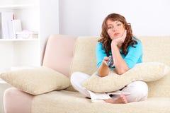Mujer triste que se sienta en el sofá con el regulador alejado Foto de archivo libre de regalías