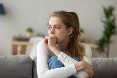 Mujer triste que se sienta en el sofá solamente en casa imágenes de archivo libres de regalías