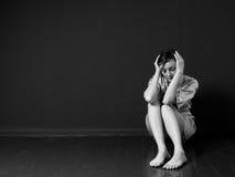 Mujer triste que se sienta en la esquina de un cuarto Imagen de archivo libre de regalías