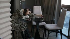 Mujer triste que se sienta en la tabla almacen de video